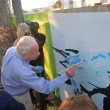 (Virginia Beach mayor Will Sessoms makes his mark with the stroke of a paint brush on 18th Street)